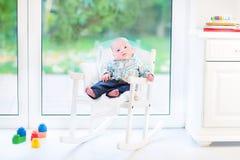 Pasgeboren babyjongen in schommelstoel volgende venster Royalty-vrije Stock Foto