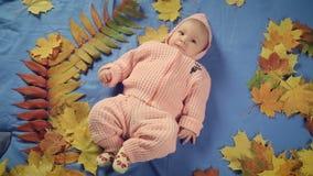 Pasgeboren babymeisje die op tapijt en de herfstbladeren liggen stock video