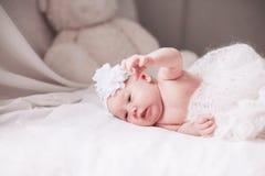 Pasgeboren babymeisje in een mooie bonnet die op een deken liggen stock foto's