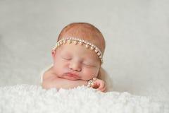 Pasgeboren Babymeisje met Bergkristal en Parelhoofdband Stock Afbeelding