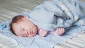 Pasgeboren babyslaap op een bed stock videobeelden