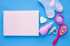 Pasgeboren babyverhaal Blocnote met copyspace en van kinderen speelgoed, schaar, zuigfles, uitsteeksel, haarborstel op blauwe ach stock afbeelding