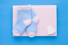 Pasgeboren babyverhaal Blocnote met copyspace en van kinderen speelgoed, schaar, zuigfles, uitsteeksel, haarborstel op blauwe ach royalty-vrije stock foto