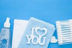 Pasgeboren babyverhaal Handdoeken en het speelgoed van kinderen, schaar, zuigfles, uitsteeksel, haarborstel op blauwe achtergrond royalty-vrije stock afbeelding