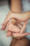 Pasgeboren babyvoeten in moederhanden Stock Foto