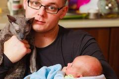 Pasgeboren die baby door vader en kat wordt gehouden Stock Foto's