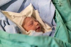 Pasgeboren, gesloten ogen, schreeuwende baby in groene deken in het ziekenhuis stock fotografie
