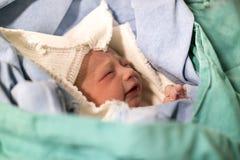 Pasgeboren, gesloten ogen, schreeuwende baby in groene deken in het ziekenhuis stock foto