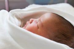 Pasgeboren het meisjesslaap van de zuigelingsbaby in bed Stock Foto's