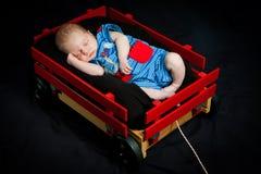 Pasgeboren Jongen In slaap in Rode Wagen stock afbeelding