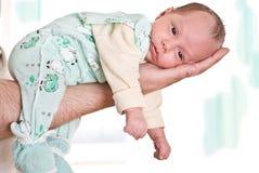 Pasgeboren leugens op het wapen van zijn vader Royalty-vrije Stock Afbeeldingen