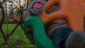 Pasgeboren leuk kind die op een binnenplaatsschommeling slingeren stock videobeelden