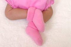 Pasgeboren meisjesvoeten in roze sokken stock afbeelding