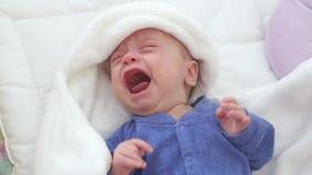Pasgeboren schreeuwende babyjongen Nieuw - het geboren kind vermoeide en hongerig in bed onder een blauwe gebreide deken stock videobeelden