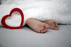 Pasgeboren slaapt onder een deken, voeten uit met een groot rood hart voor de vakantie royalty-vrije stock afbeelding