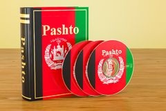 Pashto book with flag of Afghanistan and CD discs on the wooden. Table. 3D Stock Photos