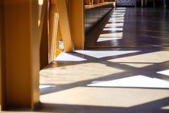 Pasillo amarillo y marrón con las sombras y los rayos de la luz triangulares con Windows imagenes de archivo