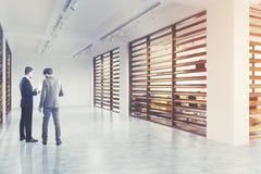 Pasillo blanco y de madera de la compañía de la pared, lado, hombres foto de archivo