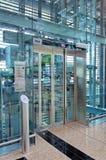 Pasillo de cristal de la elevación en el edificio del aeropuerto Fotografía de archivo