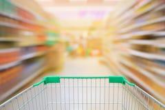 Pasillo de la falta de definición de movimiento del supermercado con el carro de la compra Foto de archivo libre de regalías