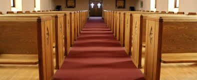 Pasillo de la iglesia cristiana tradicional con los bancos vacíos fotos de archivo