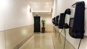Pasillo de los teléfonos públicos de la alameda Mucho teléfono negro en un pasillo de la alameda imágenes de archivo libres de regalías