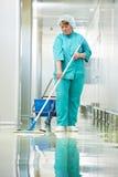 Pasillo del hospital de la limpieza de la mujer Imágenes de archivo libres de regalías