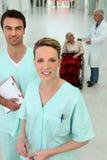 Pasillo del hospital: dos enfermeras, doctor, paciente Imágenes de archivo libres de regalías