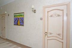 Pasillo del hotel con las puertas blancas en números y una imagen en a Fotografía de archivo libre de regalías