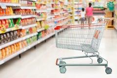 Pasillo del supermercado con el carro de la compra vacío en el colmado fotos de archivo libres de regalías