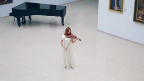 Pasillo espacioso con una mujer que toca el violín en él almacen de metraje de vídeo