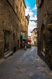 Pasillo estrecho de visita turístico de excursión en el viejo centro de ciudad de Voltera, Italia imagen de archivo