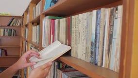 Pasillo largo de la biblioteca con los estantes para libros de madera almacen de metraje de vídeo