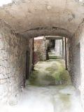 Pasillo ligero y airoso, calle estrecha, en pueblo antiguo, Italia Foto de archivo