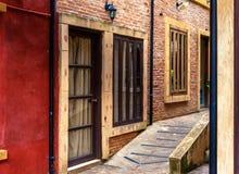 Pasillo vacío con las ventanas y las puertas en la pared de ladrillo Fotos de archivo libres de regalías