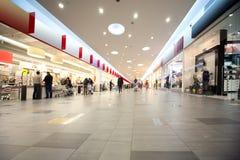 Pasillo y compradores anchos en centro comercial con los departamentos Imagen de archivo