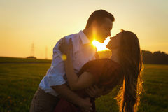 Pasion couple kisses in field at sunset Stock Image