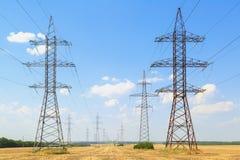 Paso de alto voltaje de las líneas eléctricas a través de campos amarillos Imagen de archivo