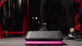 Paso de la aptitud, entrenamiento, aeróbicos, concepto del deporte - instructor atlético de la mujer en hacer del paso aerobio co almacen de video