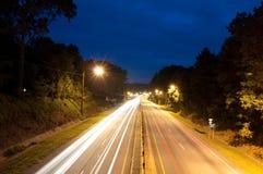 Paso de los coches en una ruta verde Foto de archivo