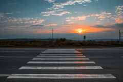 Paso de peatones fuera de la ciudad en la puesta del sol Fotografía de archivo