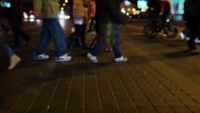 Paso de peatones que cruza de la gente en ciudad la noche de New York City enciende el fondo