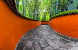 Paso entre las paredes rojas rodeadas por los bamb?es, Chengdu, China foto de archivo