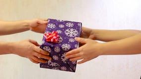 Paso masculino de la mano en las manos de la hembra de la caja de regalo de la caja almacen de video