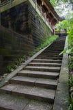 Pasos de piedra sombríos al edificio chino antiguo de la ladera Fotos de archivo libres de regalías