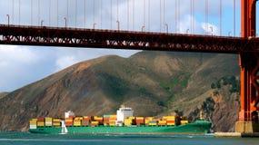Pasos de portacontenedores bajo el puente Fotografía de archivo