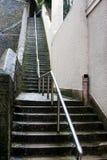 Pasos de progresión de piedra mojados deslizadizos altos con el carril de acero Foto de archivo libre de regalías