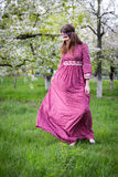 Pasos del modelo a través de la ciudad a pie Chica joven con el pelo largo en vestido rojo largo hermoso con el cordón Fotografía de archivo libre de regalías