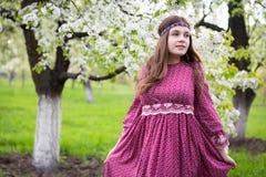 Pasos del modelo a través de la ciudad a pie Chica joven con el pelo largo en vestido rojo largo hermoso con el cordón Fotos de archivo