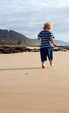 Pasos del niño en arena Fotos de archivo